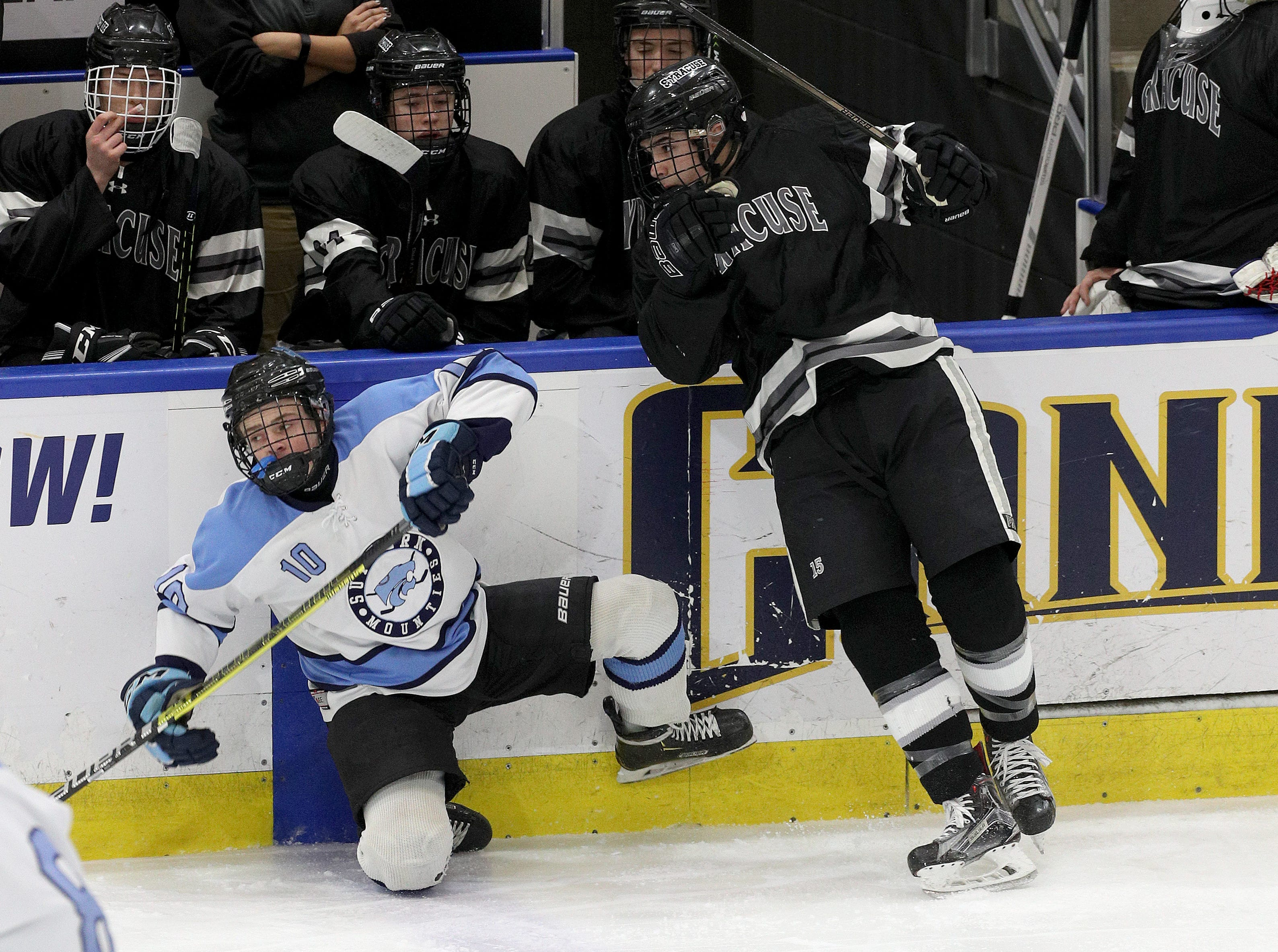 Suffern's Tommy McCarren is checked along the boards by Syracuse's Zachary Delaney.