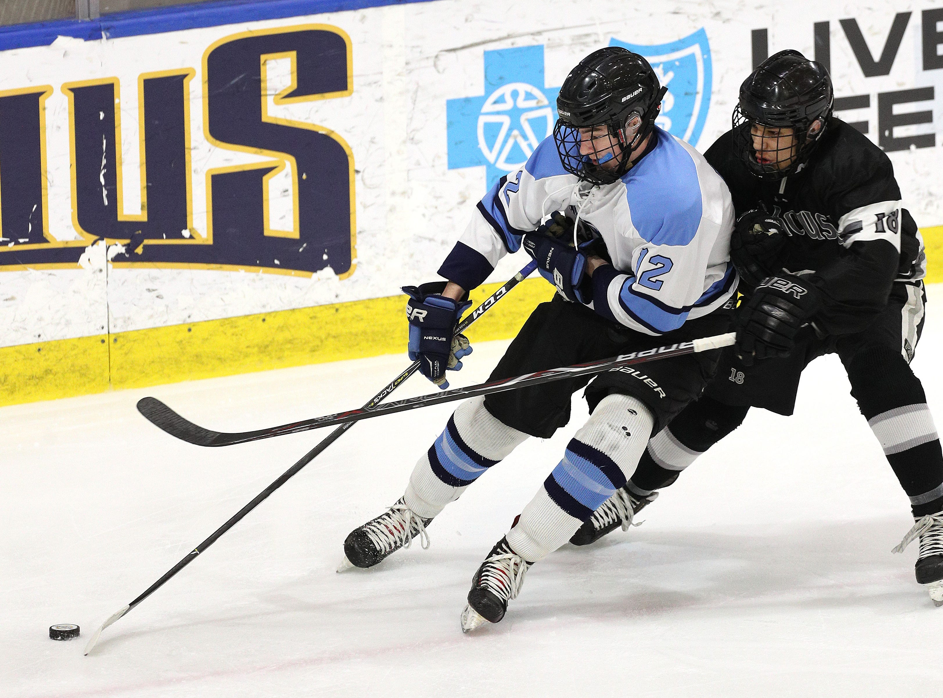 Suffern's Chris Olsen Carries the puck out of his own end and is pressured by Syracuse's Skariwate Papineau.