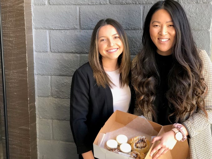Eden Bakery owners Samantha Soto and SuLaine Penick with a box of their gluten-free cinnamon rolls, French macarons, and Samoa donuts.