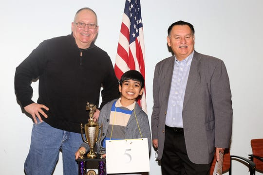 San Angelo Area Spelling Bee moderator John Flint, left, joins winner Akash Vukoti and Elks Lodge representative, Council Member Harry Thomas at the Stephens Central Library after winning in March.