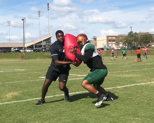 FAMU wide receivers coach Jelani Berassa works on a blocking drill with Azende Rey during practice on Saturday, March 9, 2019.