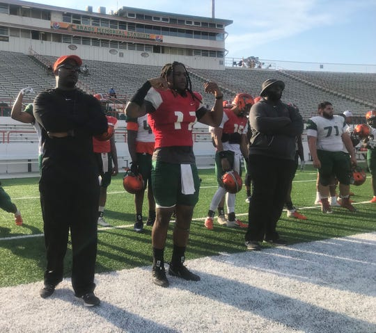 FAMU backup quarterback RaSean McKay (center) signals the plays he receives from head coach Willie Simmons (left) on Saturday, March 9, 2019. Offensive line coach Alex Jackson (right) examines the alignment.