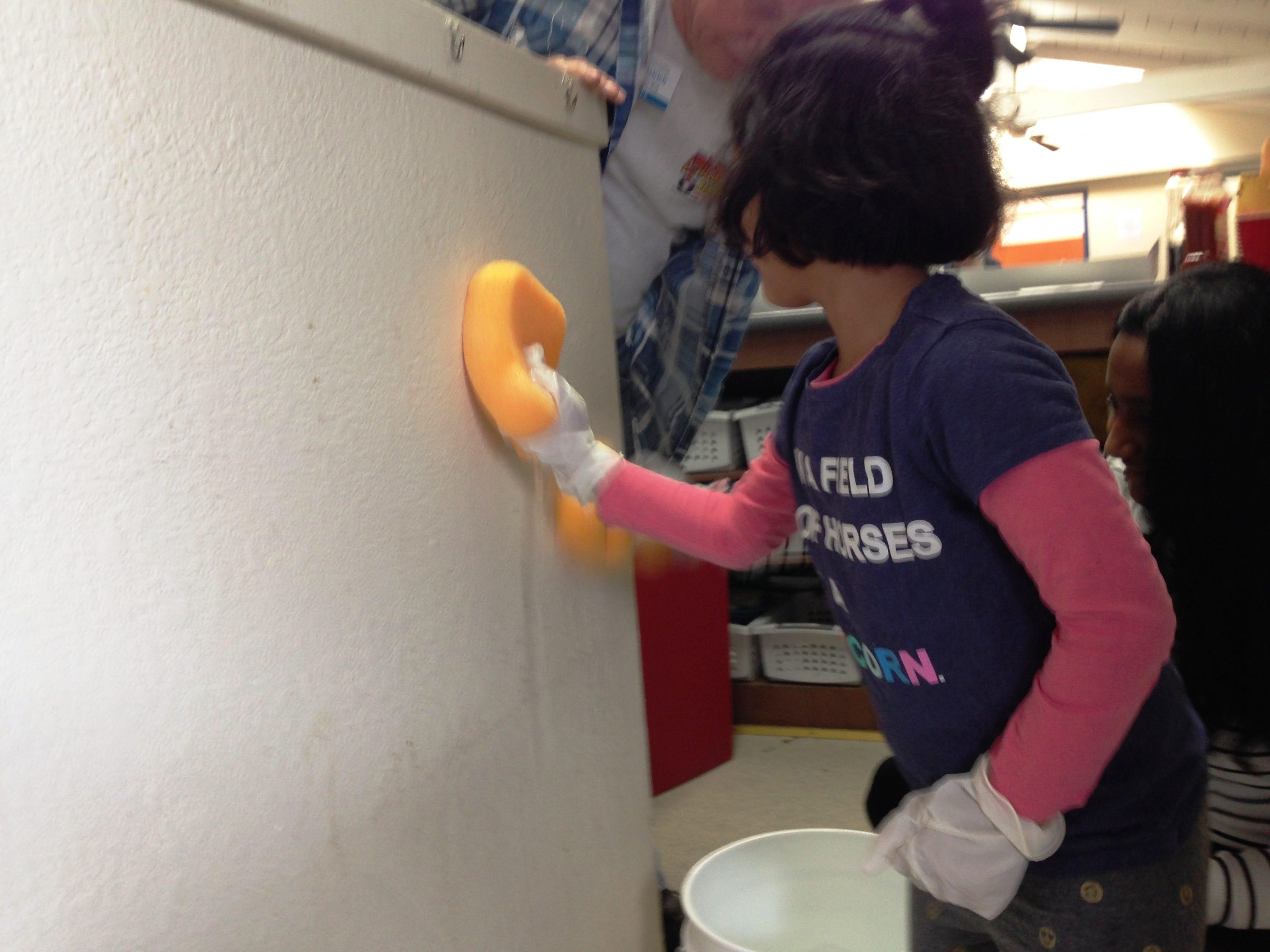 Arisha Sambari washes a wall inside the multi-purpose room at the Simi Valley Samaritan Center during Community Volunteer Day on Saturday.