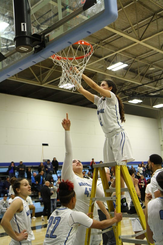 Freshman Isabel Ayala cuts down the net after the Moorpark College women's basketball team's CCCAA Southern California regional final win over Glendale on Saturday night at Raider Pavilion. Moorpark won, 79-66.