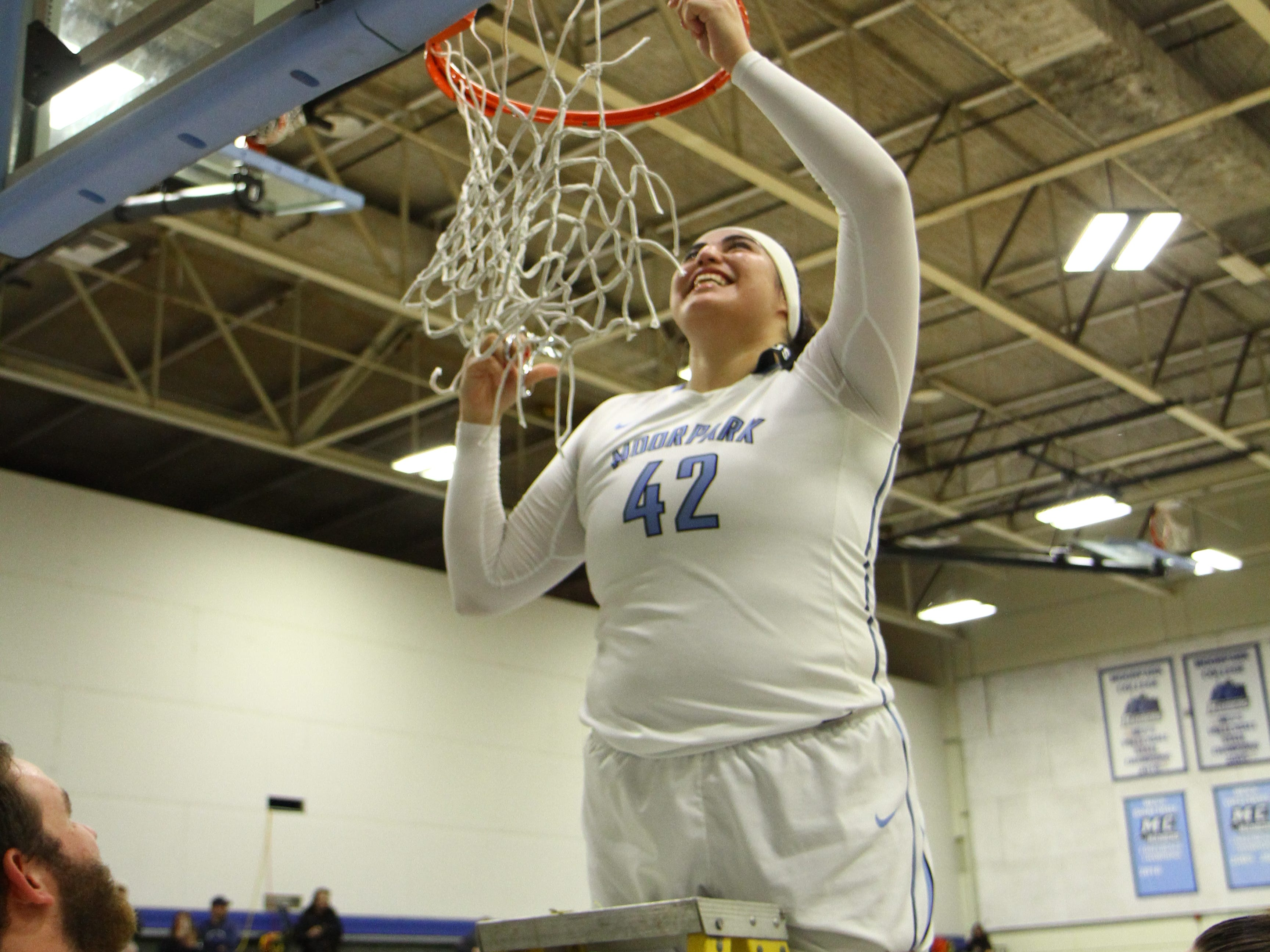 Sophomore Barbara Rangel cuts down the net after the Moorpark College women's basketball team's CCCAA Southern California regional final win over Glendale on Saturday night at Raider Pavilion.