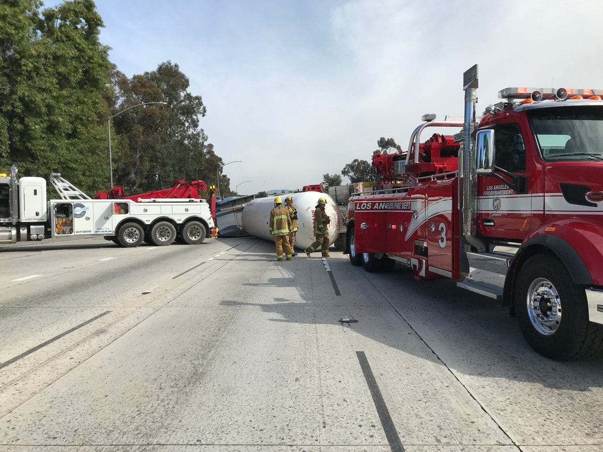 Los Angeles Fire Department crews at the scene of an overturned tanker truck on Interstate 405, north of the Highway 101 junction, on Sunday.