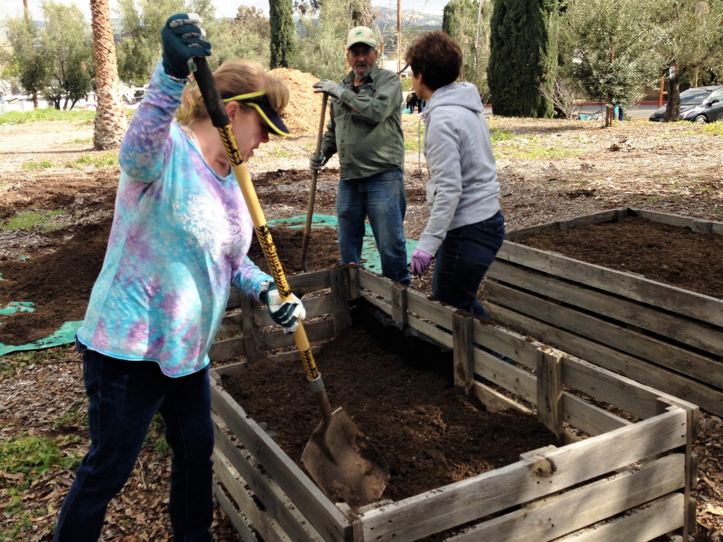Lynn Mahlmeister, Joe Santos and Lynne Kelly, all of Simi Valley, fill garden boxes with dirt at the Simi Valley Samaritan Center on Saturday during Community Volunteer Day. The garden boxes were donated by the city's community garden called Simi at the Garden.