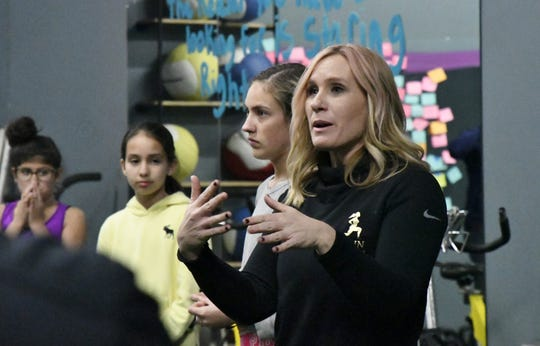 Nikki Scholl, owner of Train Like a Girl Studio, speaks with participants at a dad and daughter self-defense course on Friday, March 8, 2019.