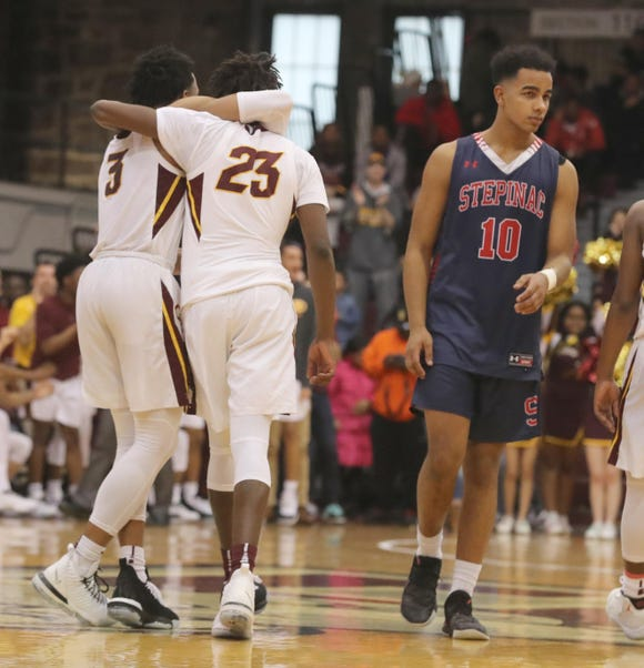 Ryan Myers and Lovell Smith of Christ the King celebrate near Sunil Fong of Stepinac in the final seconds of the the CHSAA basketball championship game at Fordham University March 10, 2019. Christ the King overcame a 14 point deficit to defeat Stepinac 61-56.