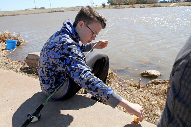 Skyler Bartels picks up corn to use for bait during Kid Fish Rodeo Saturday, March 9, 2019, at Plum Lake on Sheppard Access.