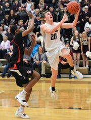 John Glenn's Parker Zachrich goes in for a layup against a Steubenville defender in Saturday's 54-51 district final loss.