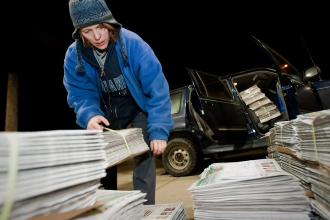A newspaper carrier loads up papers to be delivered before dawn.