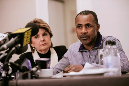 Gary Dennis, seated with lawyer Gloria Allred, speaks during a news conference.