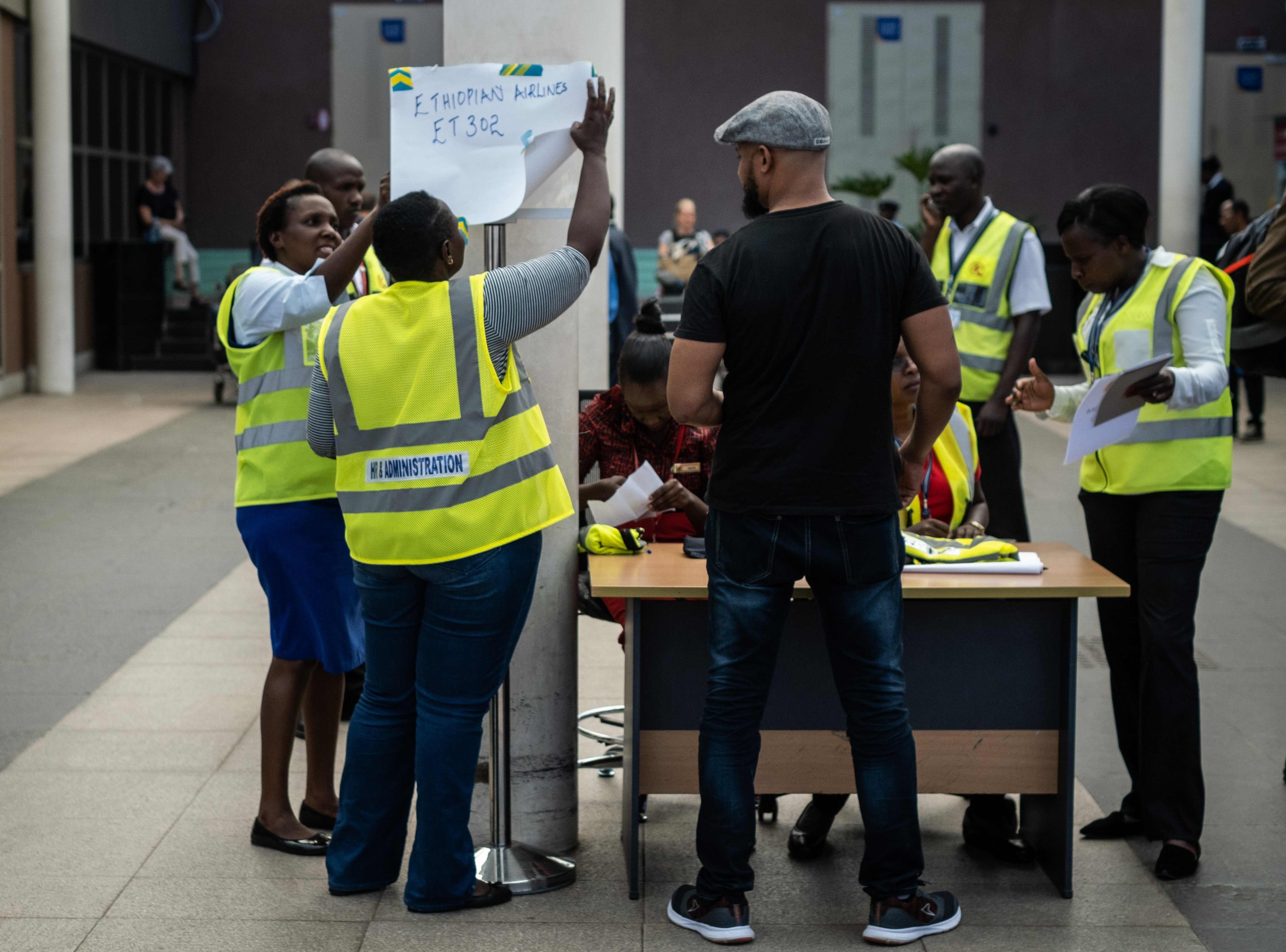 Airport staff setup a help desk at Jomo Kenyatta International Airport in Nairobi, Kenya to get information about the Ethiopia Airlines flight.