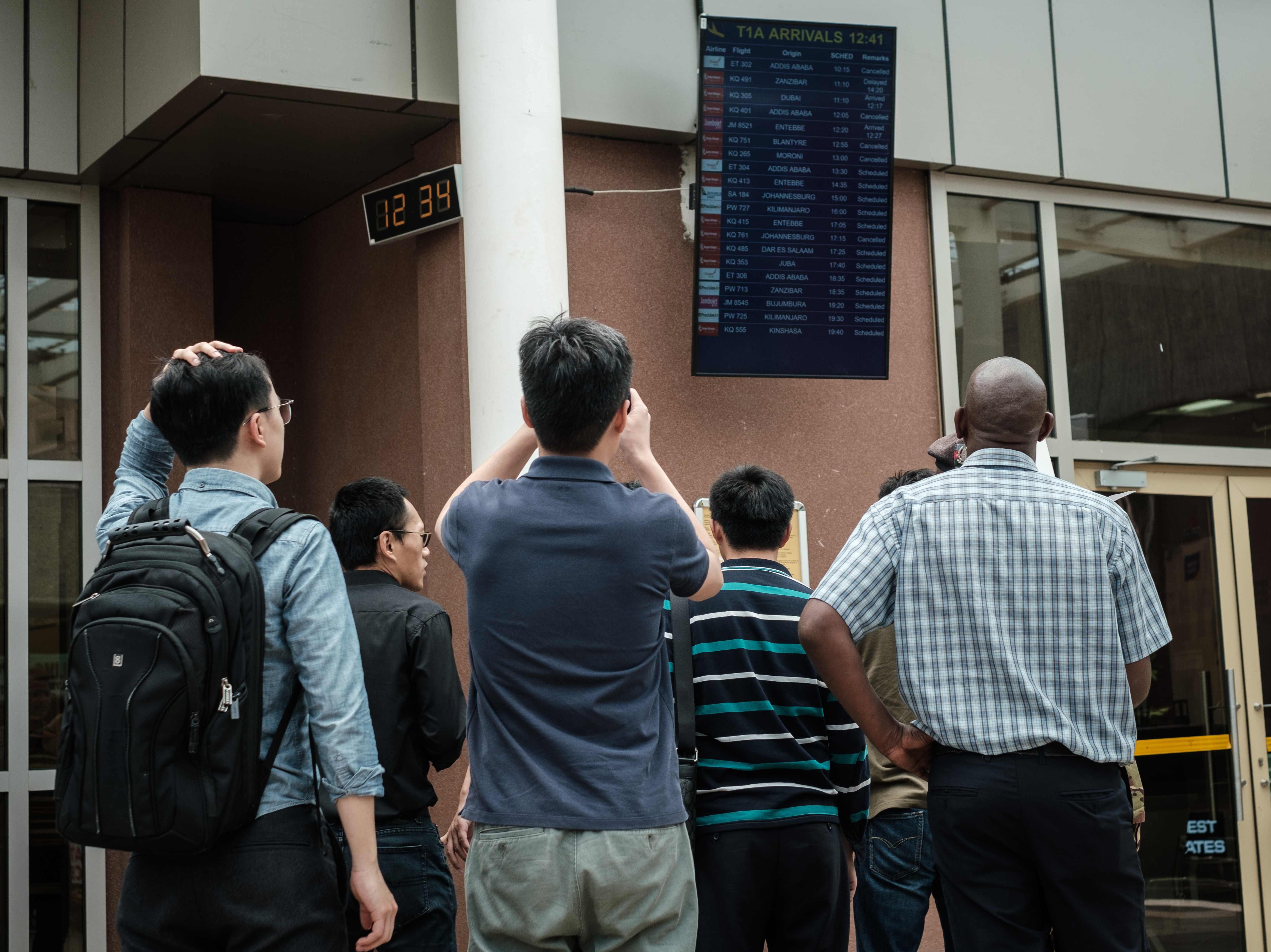 People look at the arrival flight schedule for their colleagues who were allegedly onboard the plane that crashed in Ethiopia while waiting at the Jomo Kenyatta International Airport in Nairobi, Kenya.