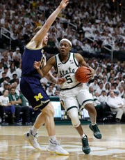 Michigan State guard Cassius Winston drives by Michigan forward Ignas Brazdeikis.