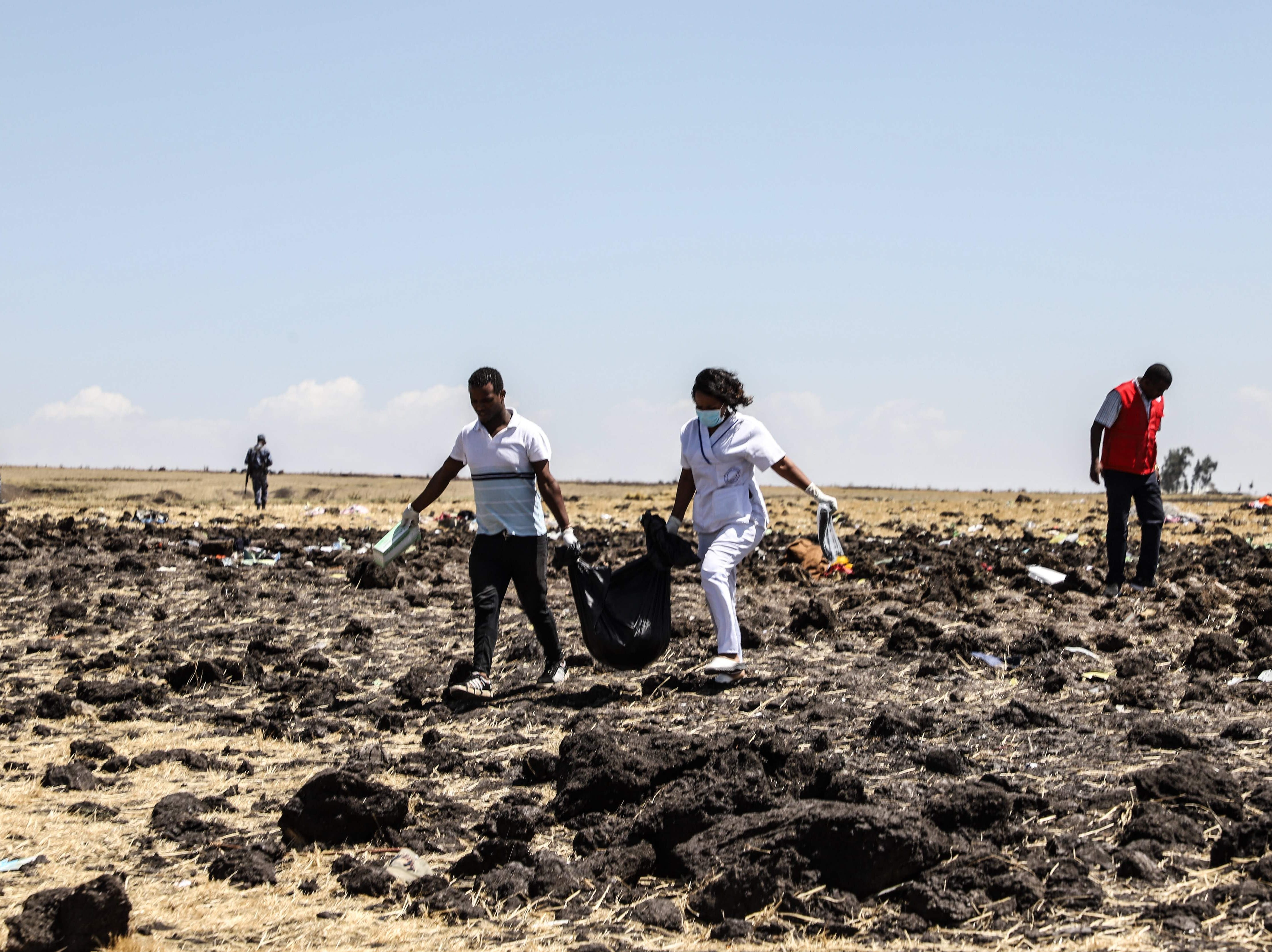 A rescue team carries a victim at the crash site of Ethiopia Airlines Flight 302 near Bishoftu, a town about 60 km southeast of Addis Ababa, Ethiopia