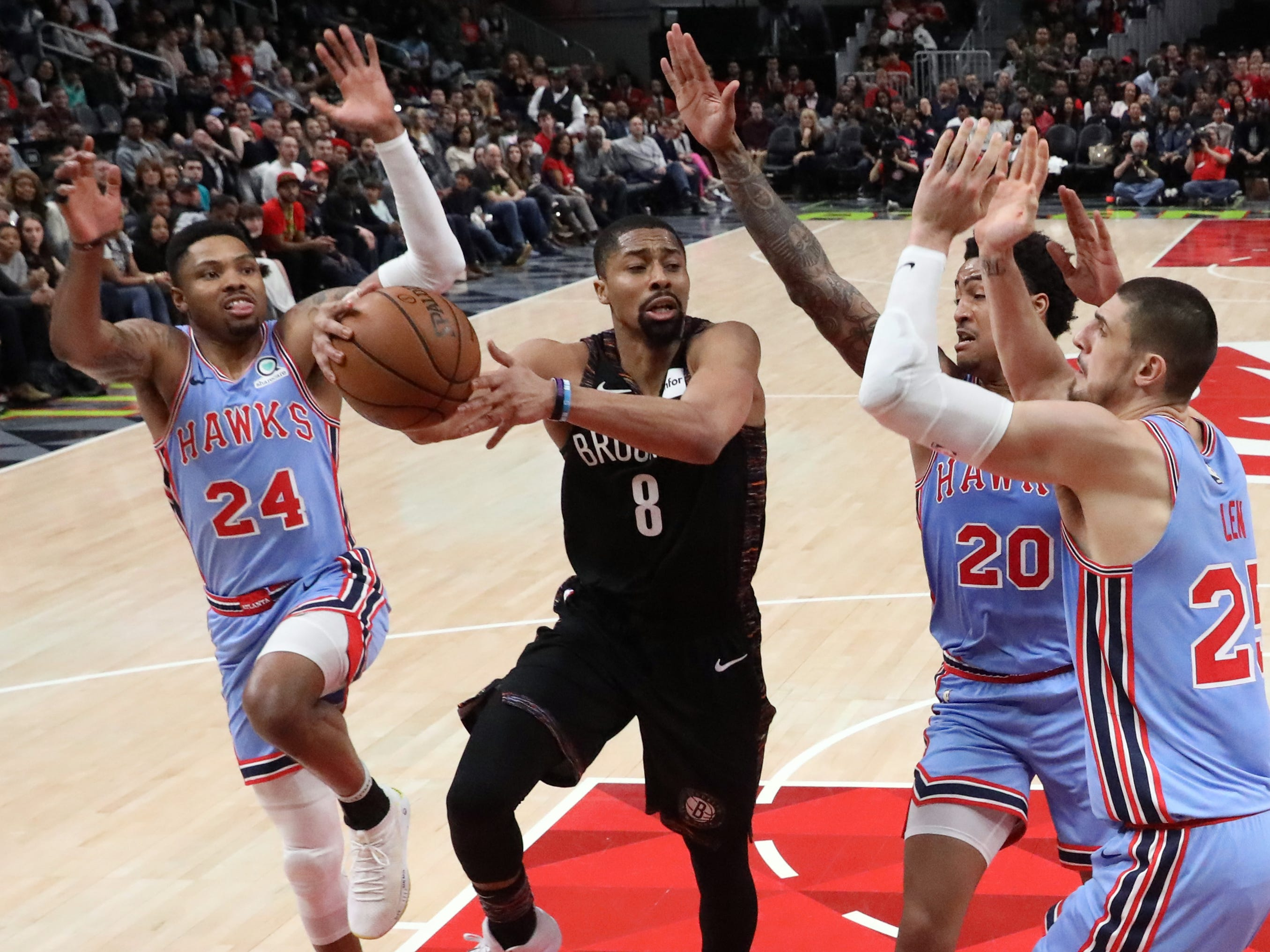 March 9: Nets guard Spencer Dinwiddie (8) looks to pass out of a triple-team by Hawks defenders Kent Bazemore (24), John Collins (20), and Alex Len (25) during the second half in Atlanta.