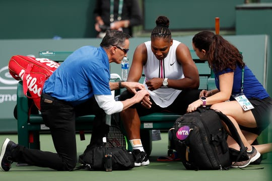 Serena Williams gets her pulse checked by a trainer before retiring from her match against Garbine Muguruza.