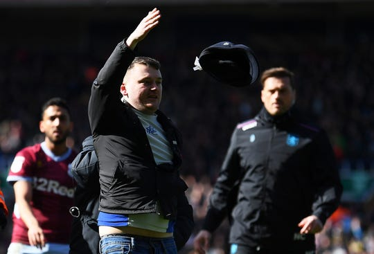 A fan is escorted off the pitch after striking Jack Grealish of Aston Villa during the Sky Bet Championship match between Birmingham City and Aston Villa at St Andrew's Trillion Trophy Stadium on March 10, 2019.