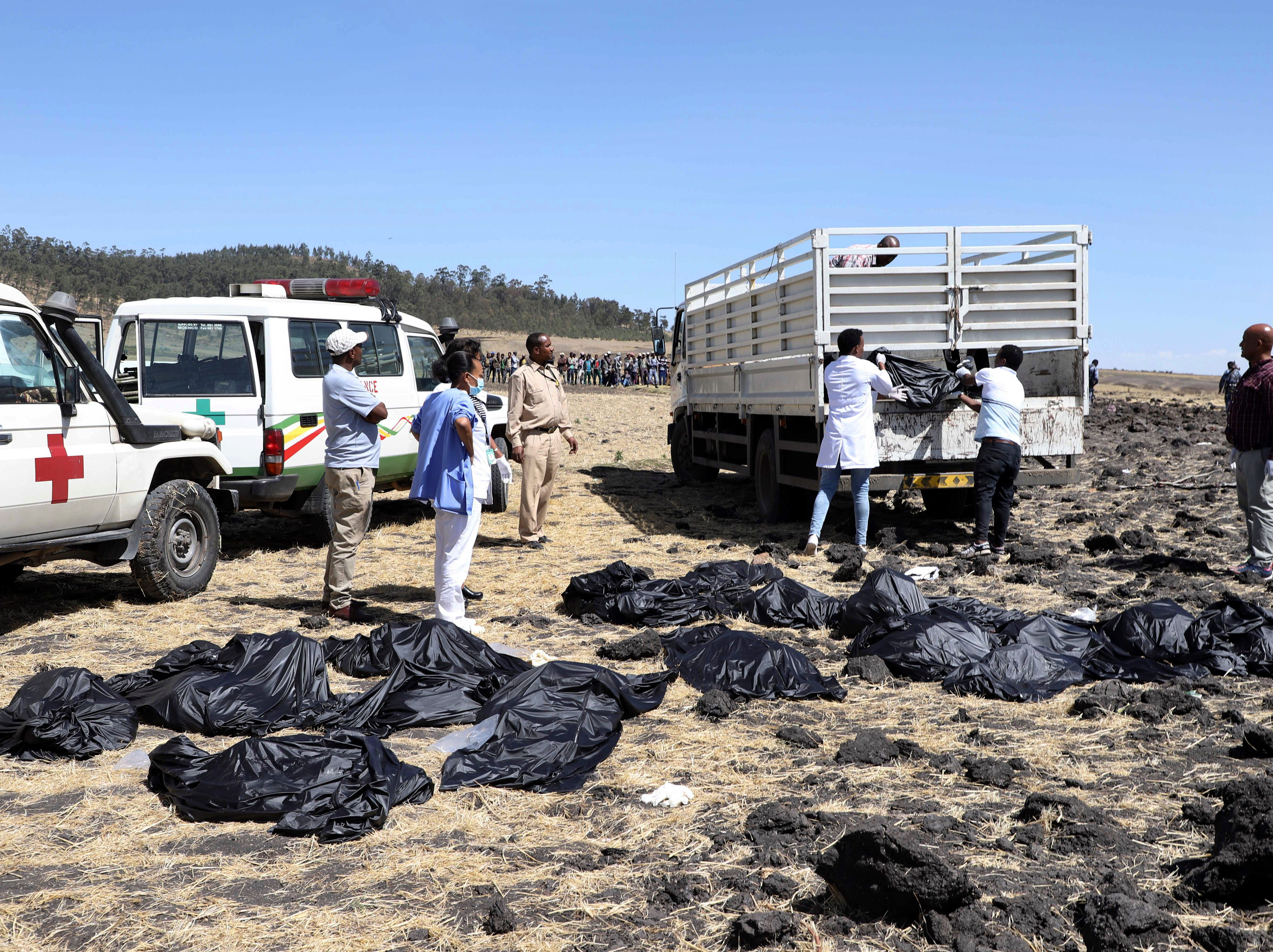 Rescuers remove body bags from the scene of an Ethiopian Airlines flight that crashed shortly after takeoff at Hejere near Bishoftu in Ethiopia.