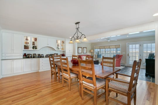 The dining room features wood flooring and custom windows.