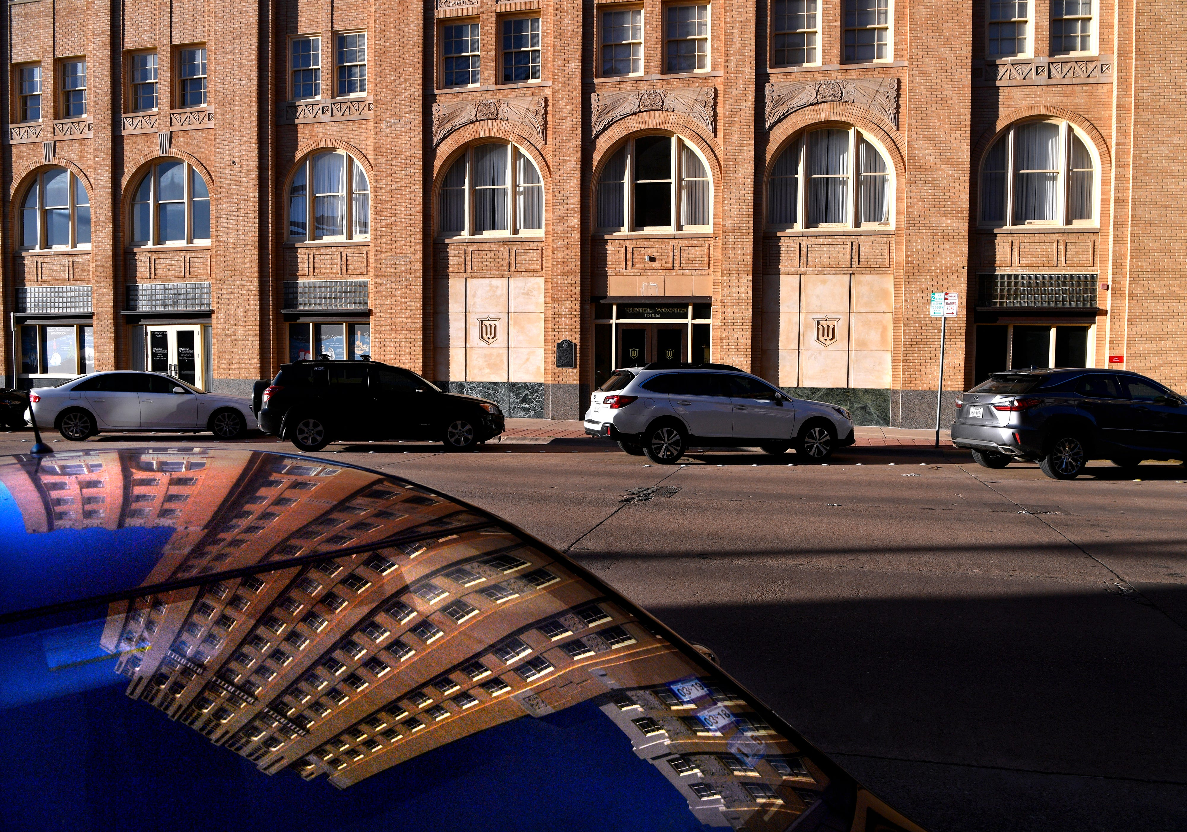 The Wooten is reflected in the windshield of a car parked in front of it, along with other vehicles filling North Third Street.
