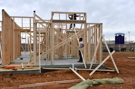 Workers erect a house frame in early March across the street from Wylie High School in south Abilene. The district is nearing 4,600 students due to continued growth in the area.