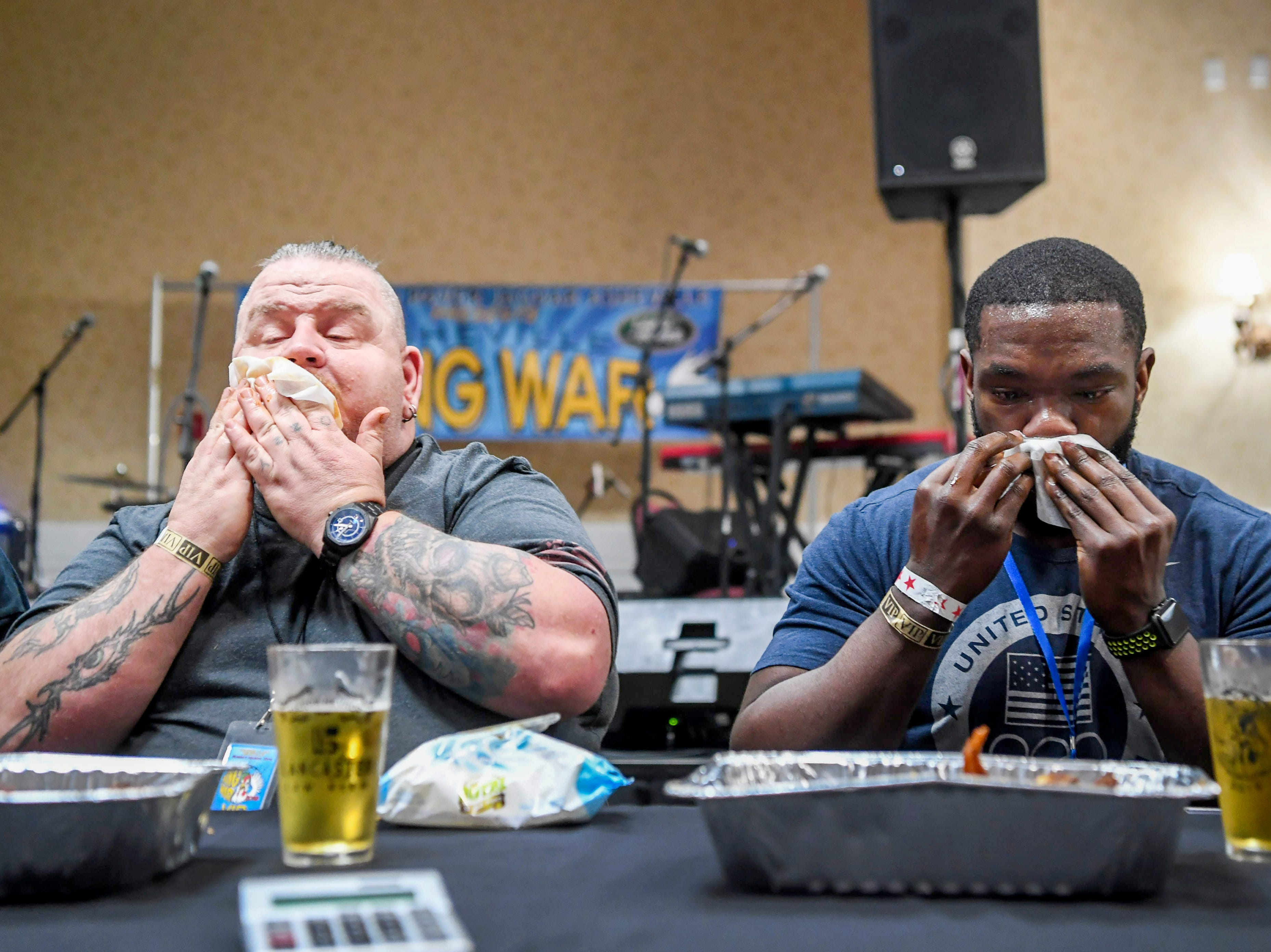 Roy Tesner, left, of Mars Hill, and Lamarcus Thicklin, of Asheville, wipe their faces as totals are counted following the King of the Wing hot wing eating contest sponsored by Firewalker Hot Sauce during the 8th annual Asheville Wing War at the Crowne Plaza March 10, 2019 in Asheville. Thicklin was later announced the winner.