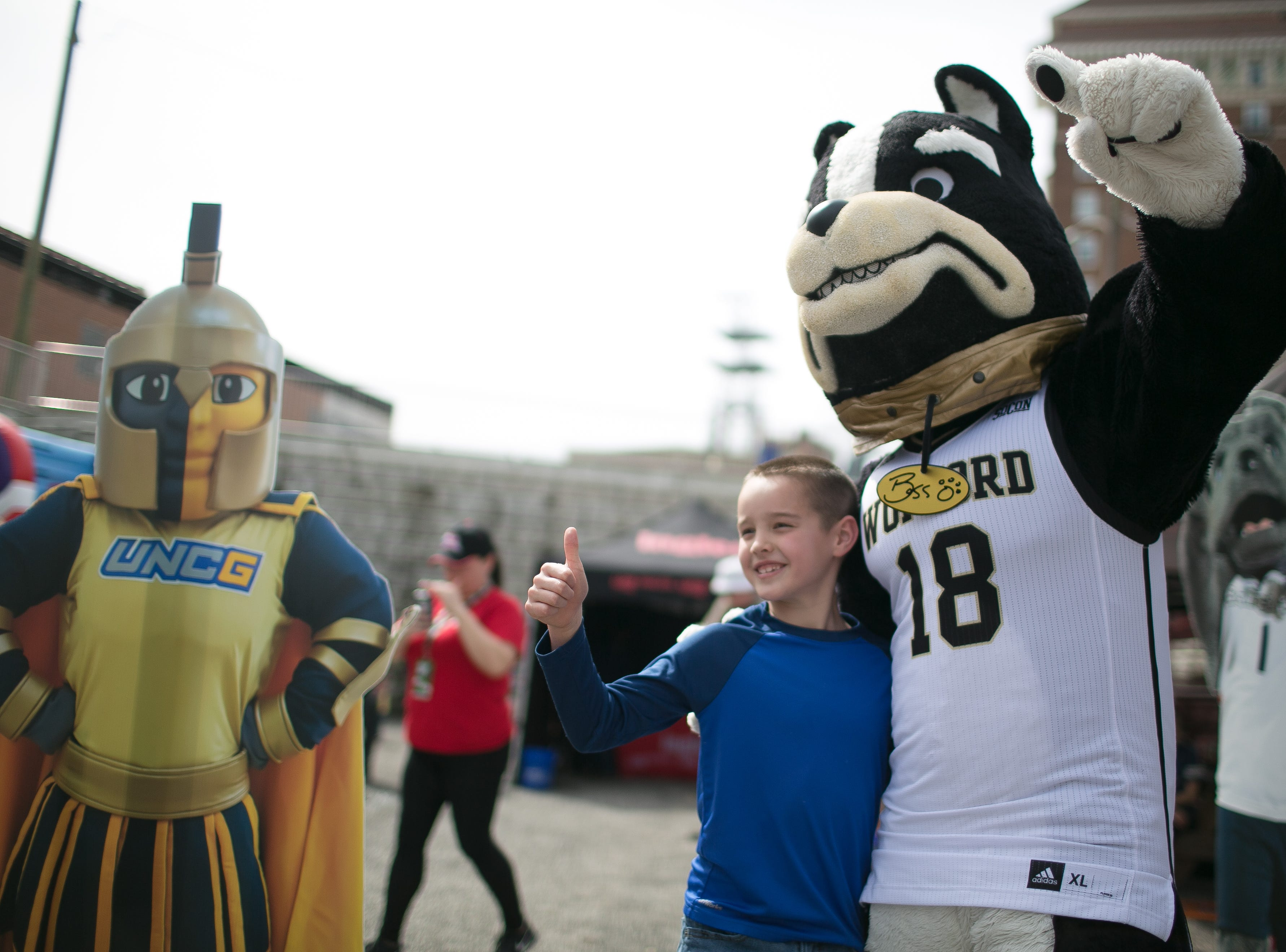 Fans greet their favorite mascots as Lyric performs at the Ingles SoCon Fan Experience  across the street from the U.S. Cellular Center, at 68 Haywood St. in downtown Asheville, on March 10, 2019.