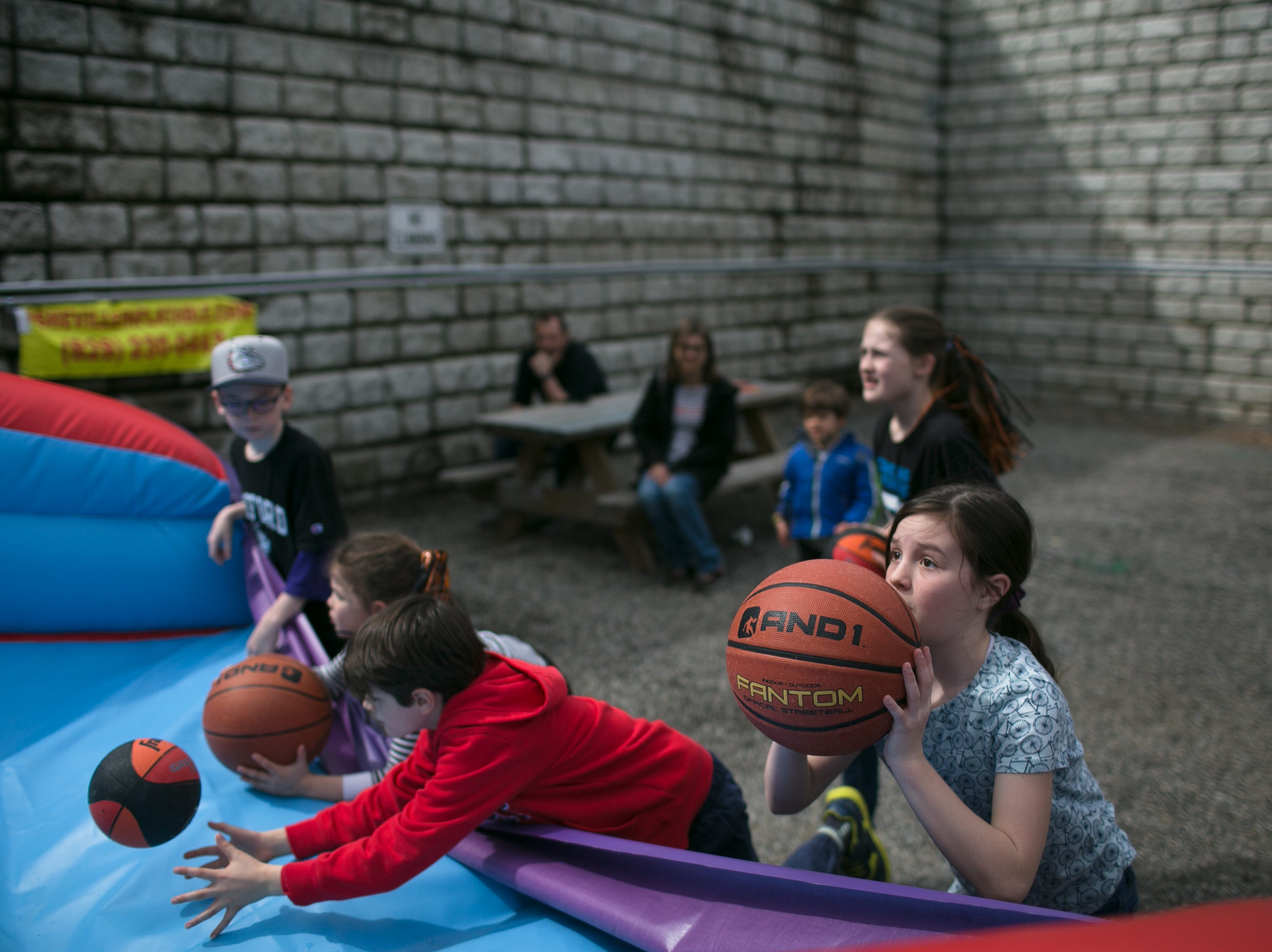 Kids play as Lyric performs at the Ingles SoCon Fan Experience  across the street from the U.S. Cellular Center, at 68 Haywood St. in downtown Asheville, on March 10, 2019.