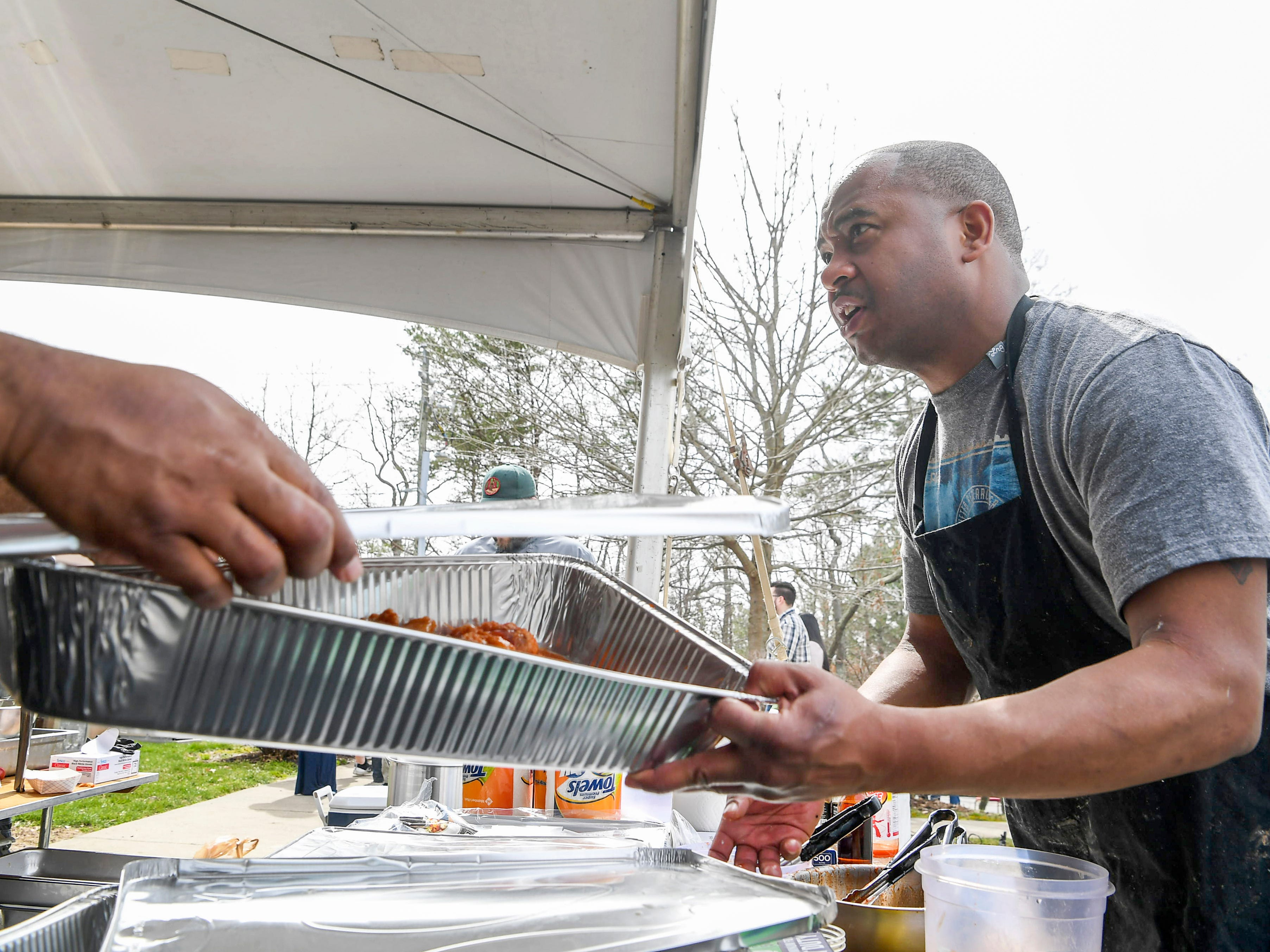 """Dominique Hunting, of Nique's Kitchen, hands off a fresh batch of """"Hazard"""" spicy chicken wings during the 8th annual Asheville Wing War at the Crowne Plaza March 10, 2019 in Asheville."""
