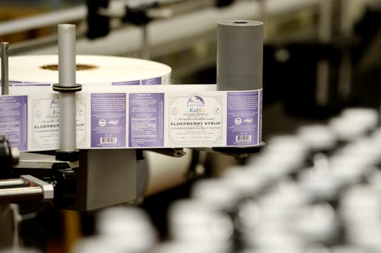 A machine is prepped to adhere labels to bottle of Darby Farms Elderberry syrup at Blue Ridge Food Ventures at AB Tech's Enka campus on Feb. 27, 2019.