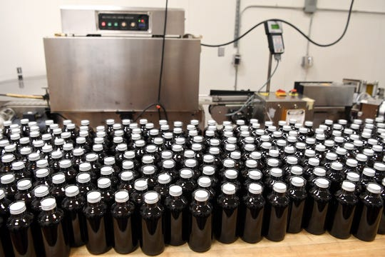 Bottles of Darby Farms Elderberry syrup await labels at Blue Ridge Food Ventures at AB Tech's Enka campus on Feb. 27, 2019.