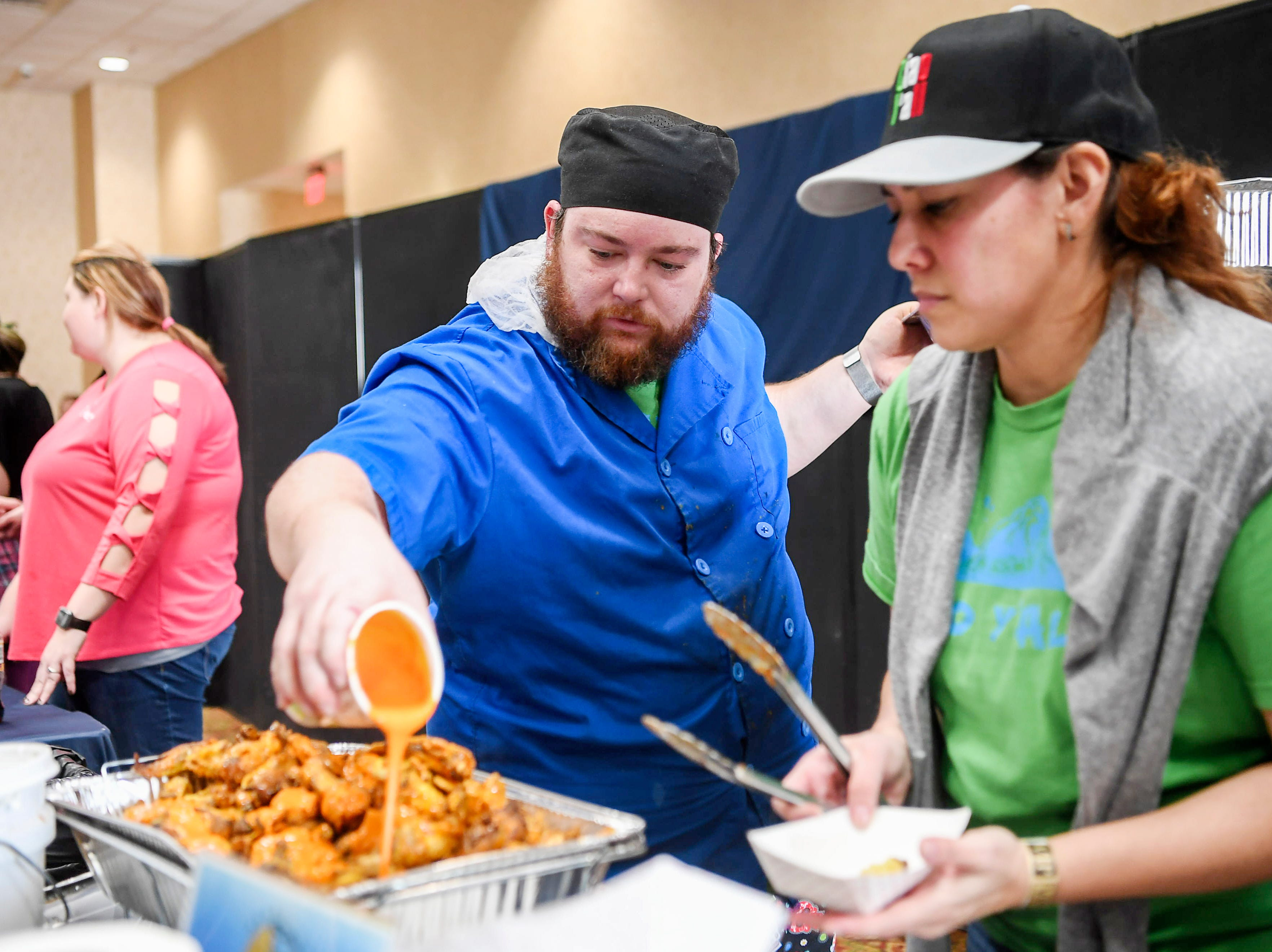 The team from the Ciao Y'all Food Truck serves up wings during the 8th annual Asheville Wing War at the Crowne Plaza March 10, 2019 in Asheville.