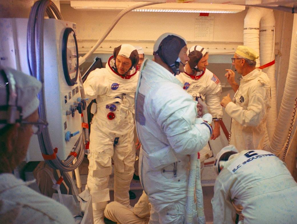 Within the White Room atop the gantry on Launch Complex 39 Pad A, the Apollo 11 astronauts egress from the Apollo spacecraft after participation in the Countdown Demonstration Test. In the foreground of the photograph is Astronaut Buzz Aldrin. Pad leader Guenter Wendt talks with Neil Armstrong.