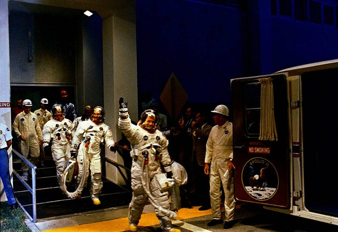 The Apollo 11 crew leaves Kennedy Space Center's Manned Spacecraft Operations Building during the pre-launch countdown. Mission commander Neil Armstrong, command module pilot Michael Collins, and lunar module pilot Buzz Aldrin prepare to ride the special transport van to Launch Complex 39A where their spacecraft awaited them.