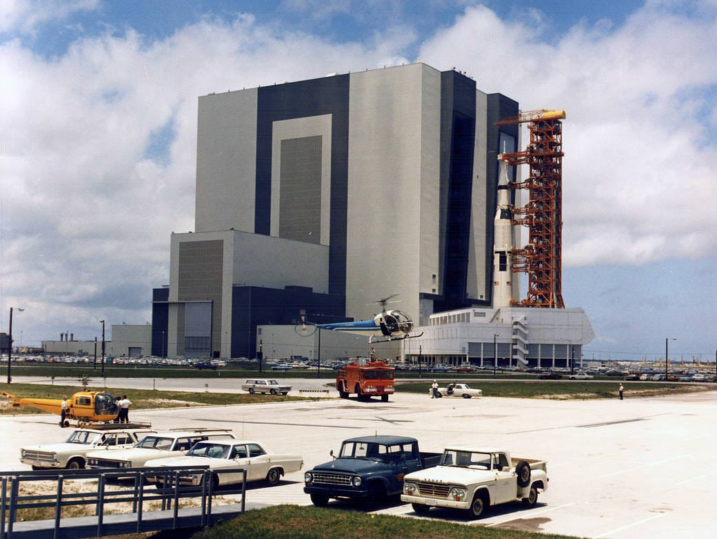 Carrying the Apollo 11 Saturn V rocket and mobile launcher, the crawler inches out of the Vehicle Assembly Building on the journey to Launch Pad 39A. The 363-foot-high space vehicle launched Apollo 11 astronauts Neil A. Armstrong, Michael Collins and Edwin E. Aldrin Jr. on the first manned lunar landing