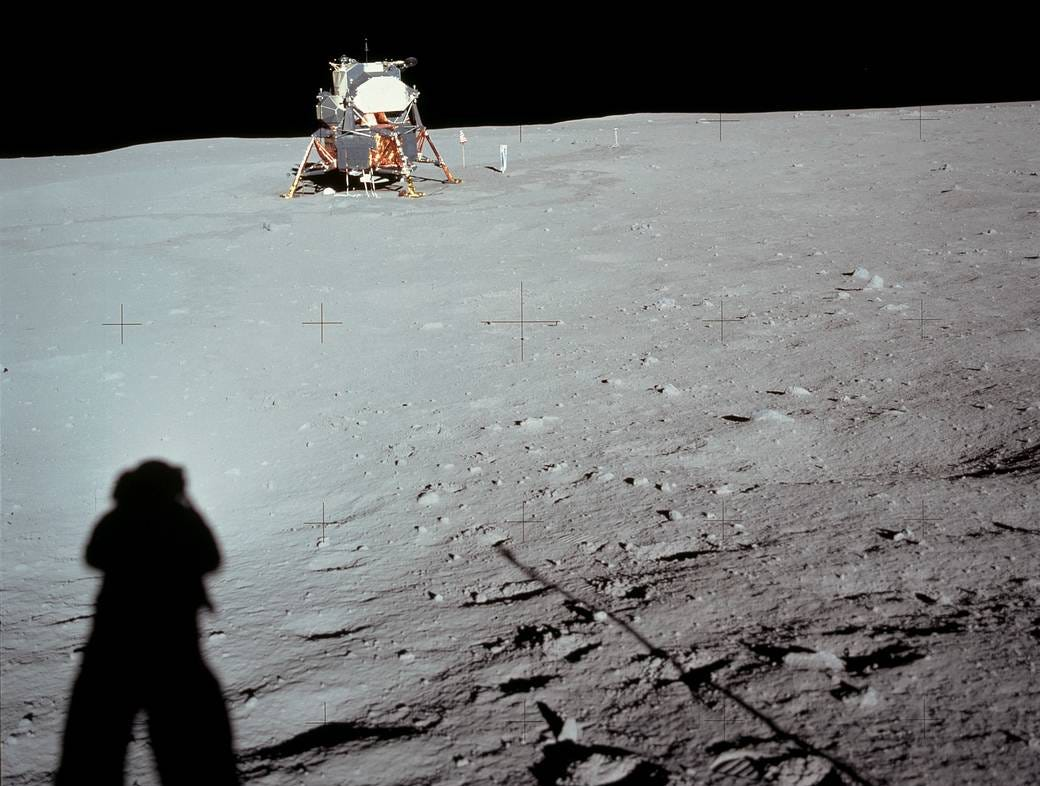 This photograph of the Lunar Module at Tranquility Base was taken by Neil Armstrong during the Apollo 11 mission, from the rim of Little West Crater on the lunar surface. Armstrong's shadow and the shadow of the camera are visible in the foreground. This is the furthest distance from the lunar module traveled by either astronaut while on the moon.