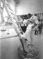 In preparation of the nation's first lunar landing mission, Apollo 11 crew members underwent training to practice activities they would be performing during the mission. In this photograph, Neil Armstrong, in his spacesuit, practices getting back to the first rung of the ladder on the lunar module.