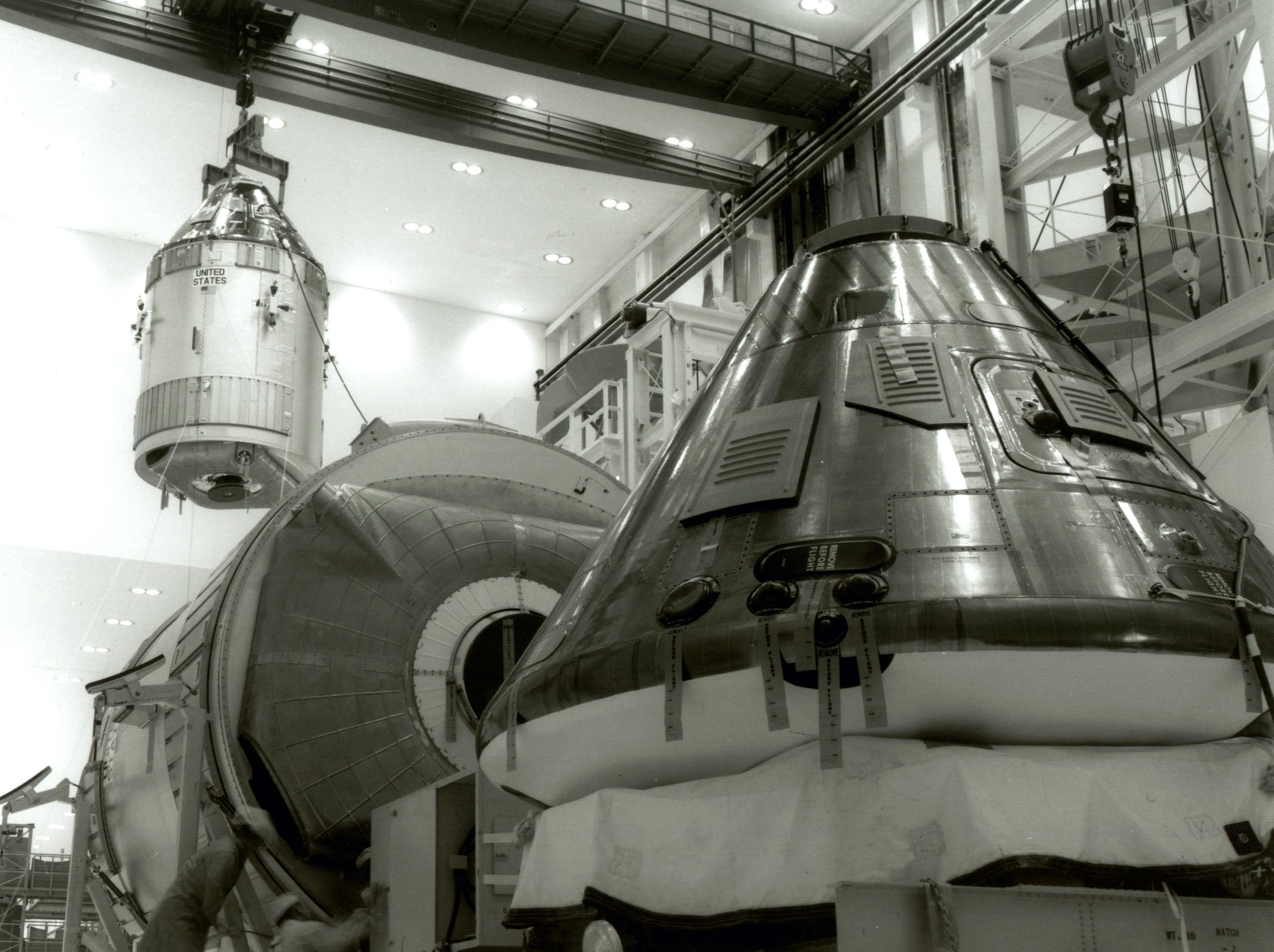 The command module and service module for the Apollo 11 mission are moved to the work stand in preparation for the first manned lunar landing.