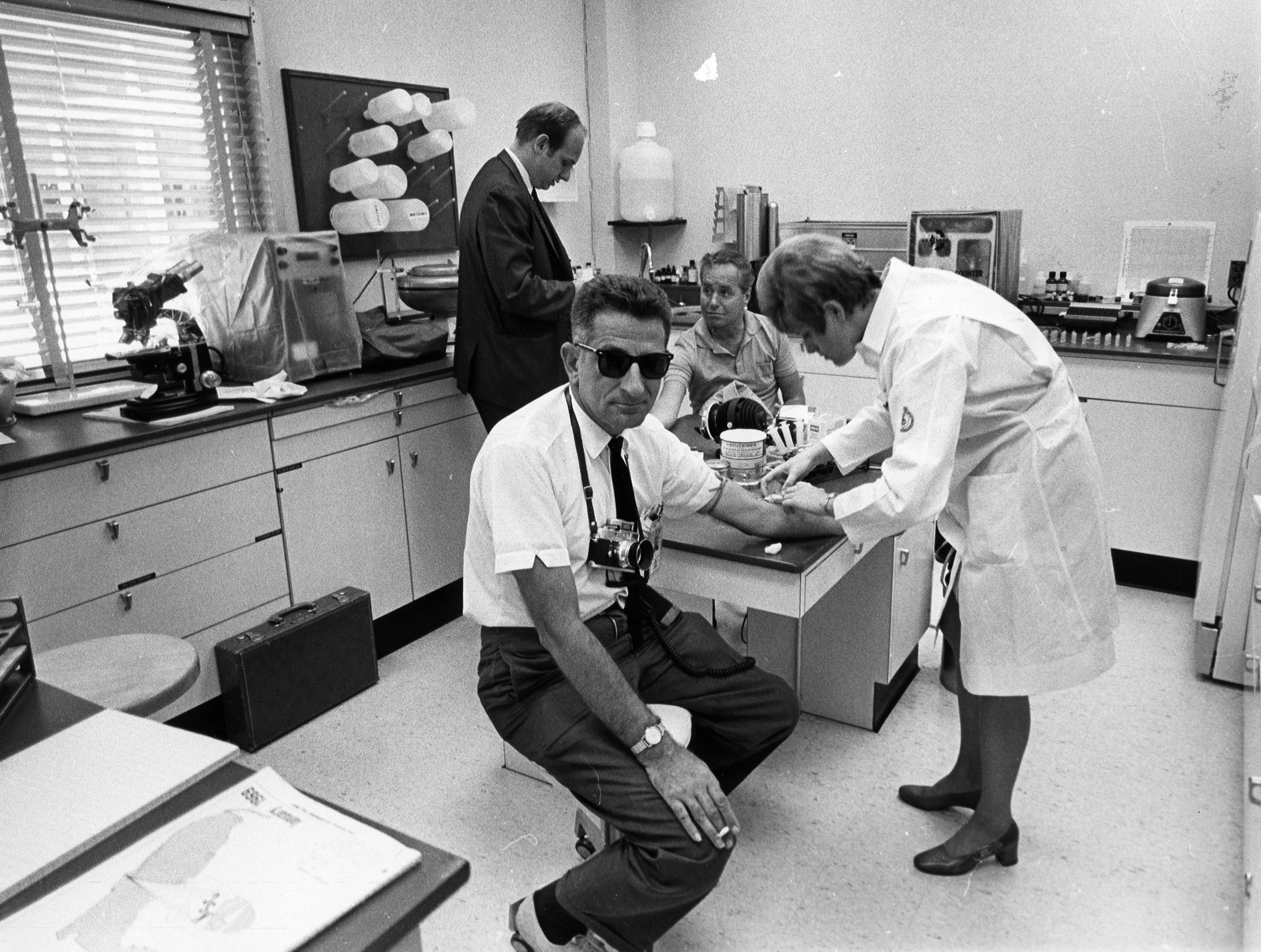 In keeping with the semi-quarantine for the Apollo 11 mission, NASA photographer Bill Taub having blood test prior to photographing the Apollo 11 crew - Neil A. Armstrong, Michael Collins and Edwin E. Aldrin, Jr. Administering the blood test in the Launch Site Medical Operations Laboratory is Cheryl Tuchman.