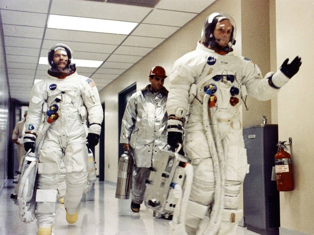 Apollo 11 Commander Neil A. Armstrong waves to well-wishers in the hallway of the Manned Spacecraft Operations Building as he and Michael Collins and Edwin E. Aldrin Jr. prepare to be transported to Launch Complex 39A for the first manned lunar landing mission.