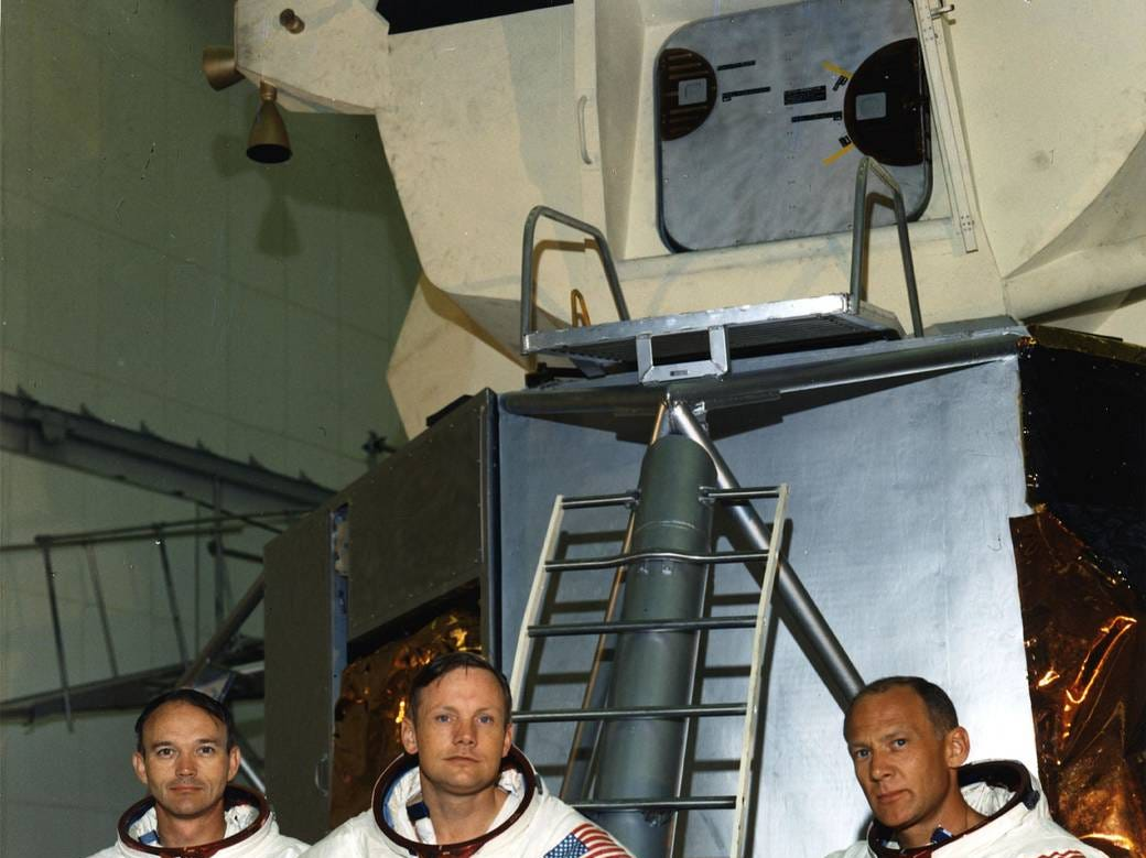 As the Apollo 11 astronauts rehearse their lunar landing mission in simulators, they pause in front of a lunar module mockup in the Flight Crew Training Building area. From left, are Command Module Pilot Michael Collins, Commander Neil A. Armstrong, and Lunar Module Pilot Edwin E. Aldrin, Jr.