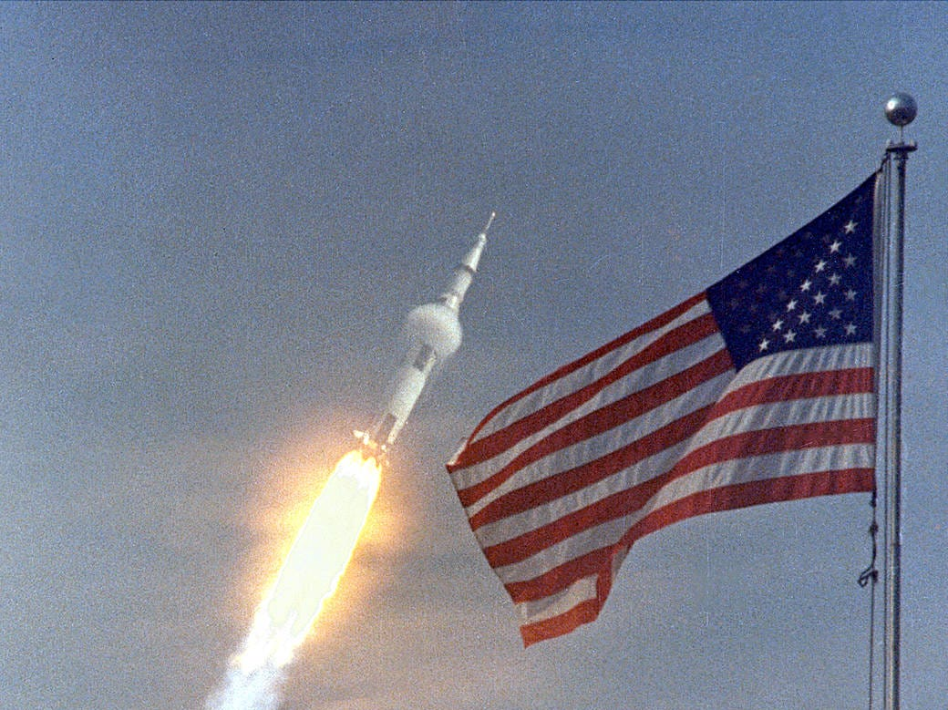 """The American flag heralded the launch of Apollo 11, the first Lunar landing mission, on July 16, 1969. The massive Saturn V rocket lifted off from NASA's Kennedy Space Center with astronauts Neil A. Armstrong, Michael Collins, and Edwin """"Buzz"""" Aldrin at 9:32 a.m. EDT. Four days later, on July 20, Armstrong and Aldrin landed on the Moon's surface."""
