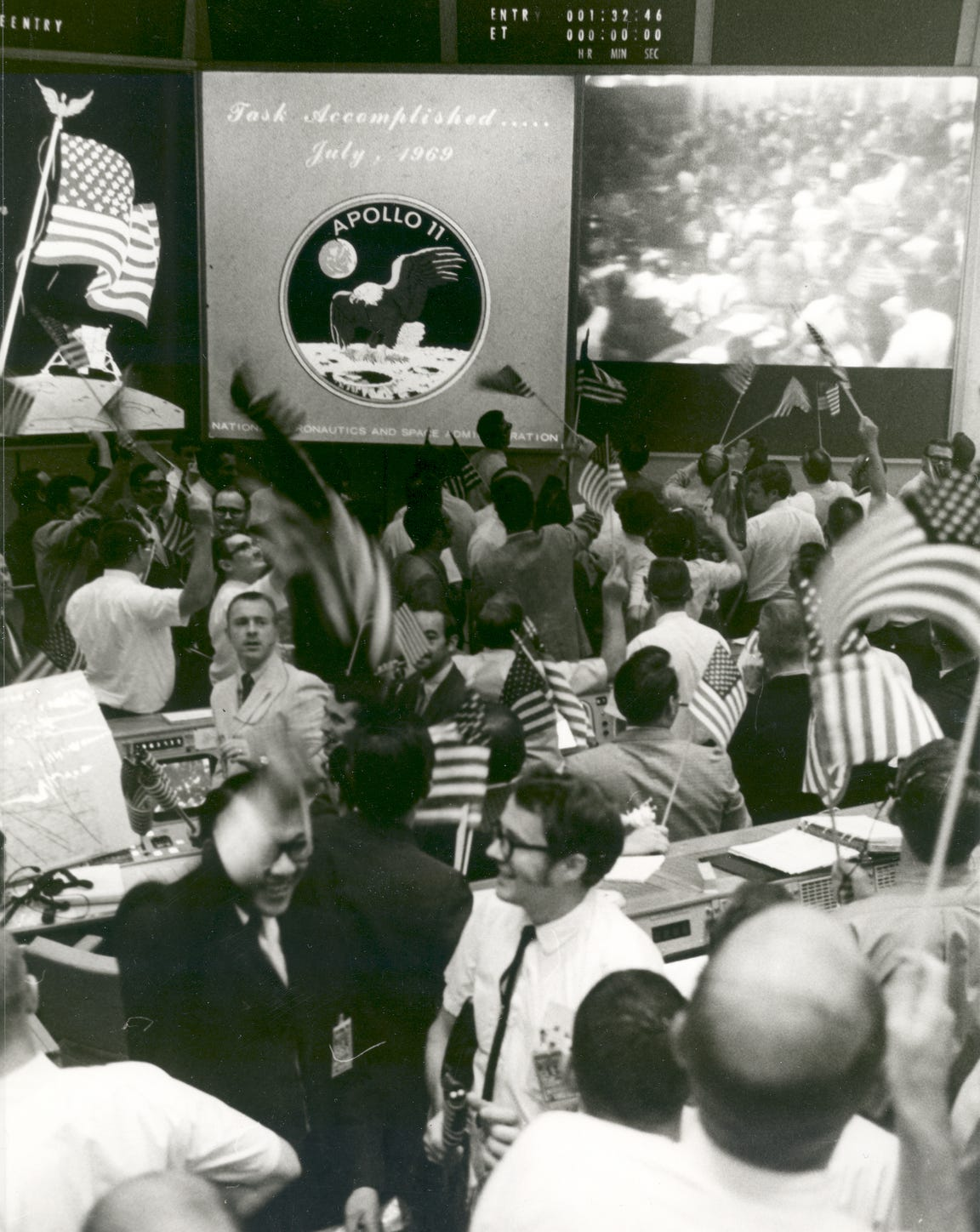 In the Mission Operations Control Room of the Mission Control Center, Building 30, Manned Spacecraft Center, flight controllers applaud the splashdown and success of the Apollo 11 lunar mission. Four days earlier on July 20, 1969, mission commander Neil Armstrong and lunar module pilot Buzz Aldrin landed on the moon.
