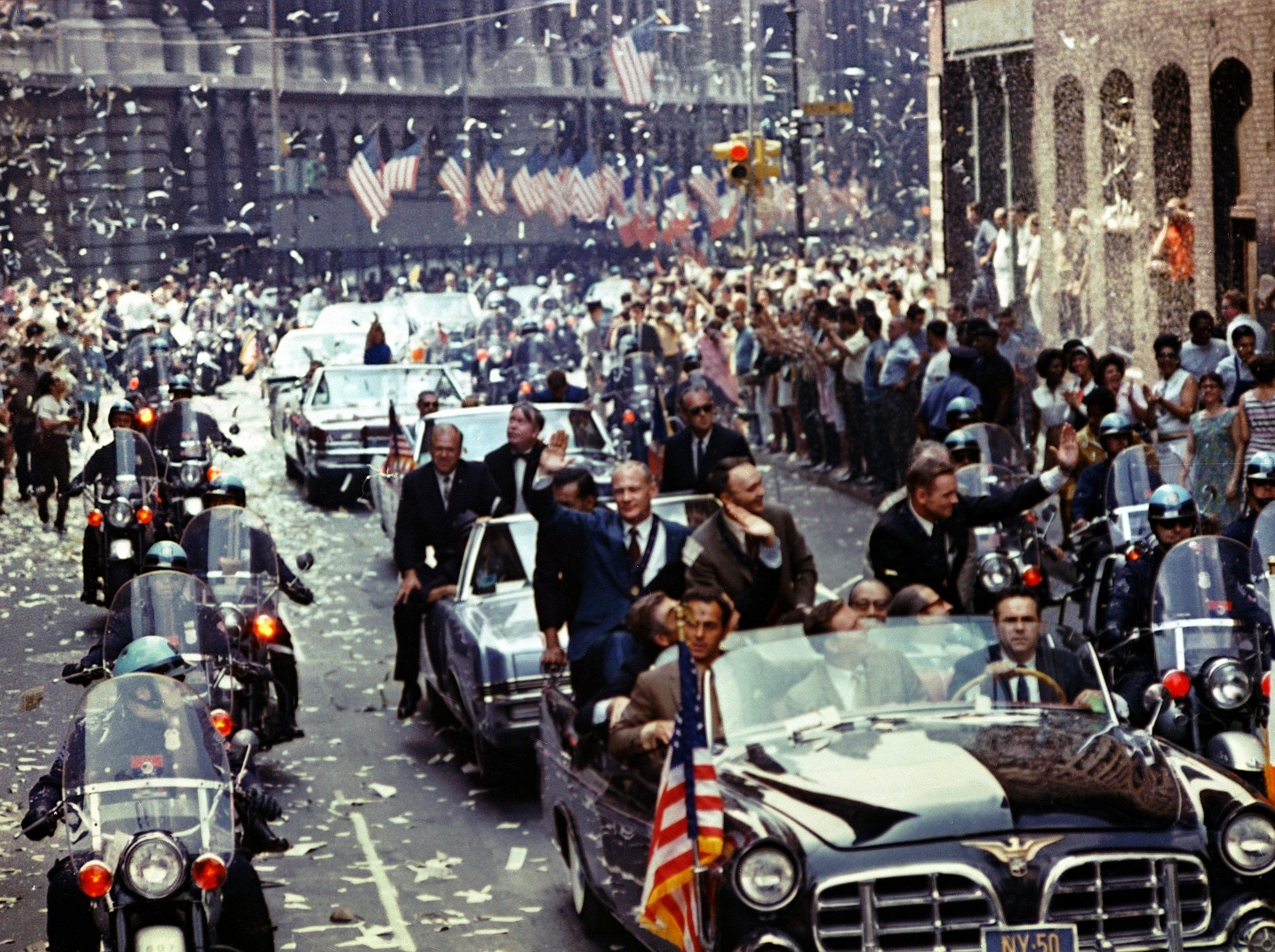 New York City welcomes Apollo 11 crewmen in a showering of ticker tape down Broadway and Park Avenue in a parade termed as the largest in the city's history. Pictured in the lead car, from the right, are astronauts Neil A. Armstrong, commander; Michael Collins, command module pilot; and Edwin E. Aldrin Jr., lunar module pilot.
