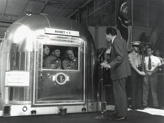 "The Apollo 11 astronauts, left to right, Commander Neil A. Armstrong, Command Module Pilot Michael Collins and Lunar Module Pilot Edwin E. ""Buzz"" Aldrin Jr., inside the Mobile Quarantine Facility aboard the USS Hornet, listen to President Richard M. Nixon on July 24, 1969 as he welcomes them back to Earth and congratulates them."