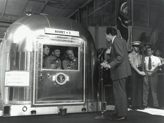 """The Apollo 11 astronauts, left to right, Commander Neil A. Armstrong, Command Module Pilot Michael Collins and Lunar Module Pilot Edwin E. """"Buzz"""" Aldrin Jr., inside the Mobile Quarantine Facility aboard the USS Hornet, listen to President Richard M. Nixon on July 24, 1969 as he welcomes them back to Earth and congratulates them."""