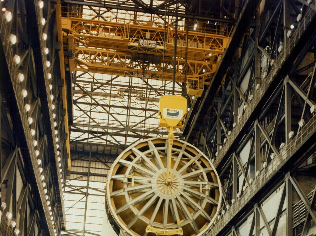 An overhead crane lifts the Saturn V first stage for the Apollo 11 mission from the transfer aisle floor in preparation for stacking on a mobile launcher inside the Vehicle Assembly Building's High Bay 1. The 138-foot-long stage, to which two additional stages were added, generated a liftoff thrust of 7.7 million pounds.